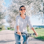 A lady bicycling on a street on a beautiful day.
