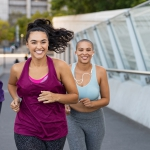 Three young women exercising by running in the city.