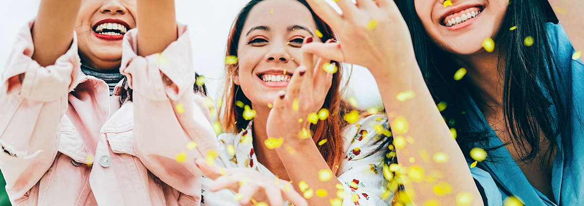 Three young asian women throwing confetti in excitement.