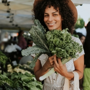 Young lady holding fresh kale leaves at an outdoor market.