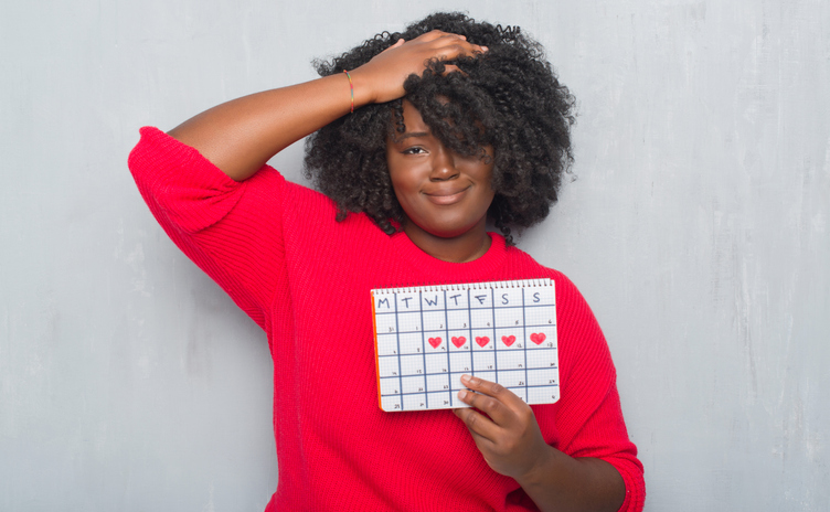 Young african american woman over grey grunge wall holding menstruation calendar.