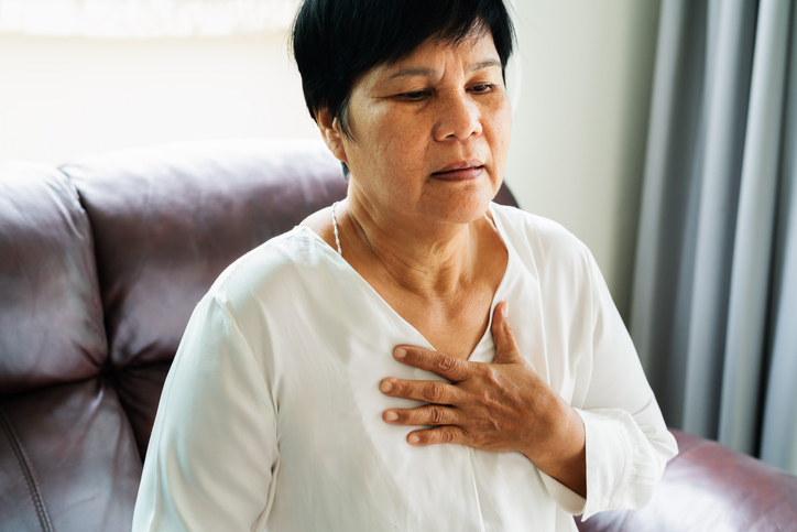 old woman having heart attack and grabbing her chest, dealing with heart disease in women.