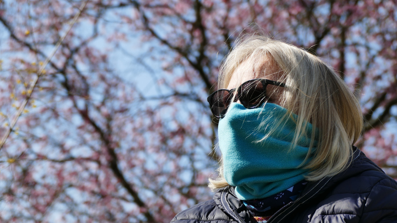 A woman wearing a facemask with cherry blossoms behind her.