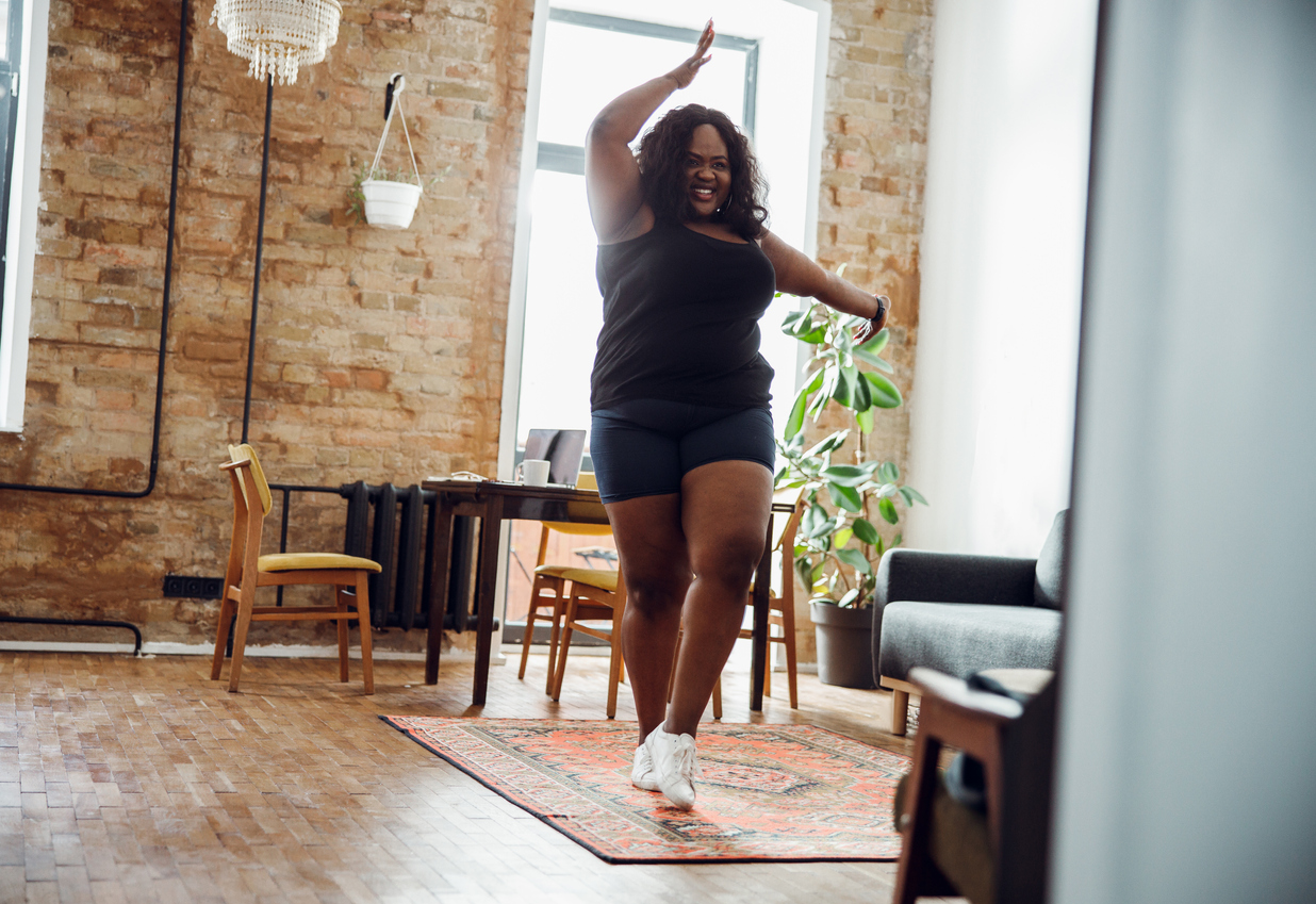 Happy woman with excess weight smiling and dancing alone in sports clothes, knowing Being Active Can Positively Impact Women's Health.