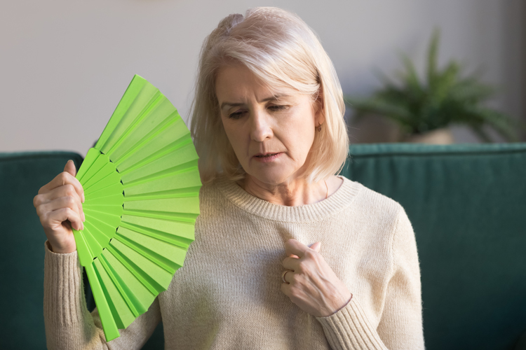 An older woman fanning herself from hot flashes.
