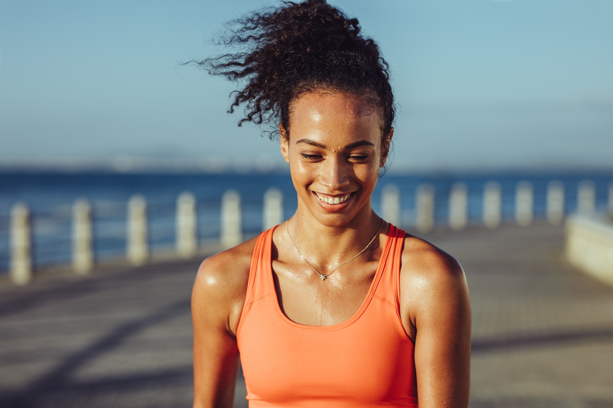 Smiling young female runner taking a breather. Healthy young woman with sweat standing on the promenade after her workout and smiling, wondering about sweating down there.