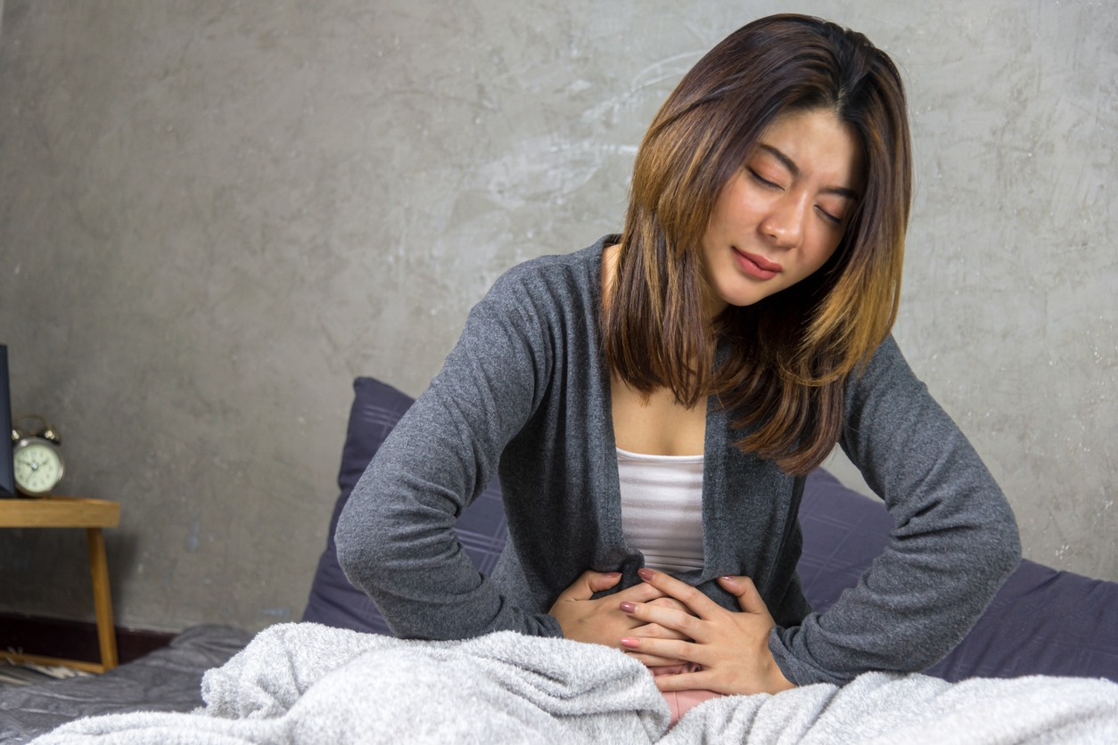 Woman sitting on Bed and feeling spasm and symptoms of polycystic ovary syndrome.