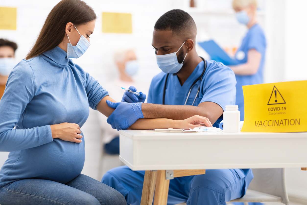 Covid-19 Vaccination Concept. Pregnant Woman Receiving Coronavirus Vaccine Intramuscular Injection Shot In Arm, Sitting With Black Nurse In Hospital Room. Covid 19 Virus Protection Medical Campaign.