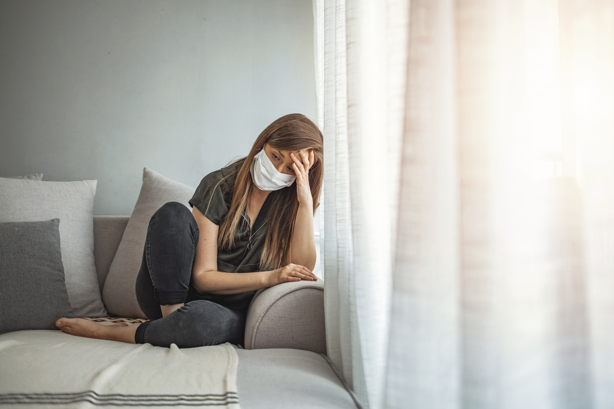 Sad lonely girl isolated stay at home in protective sterile medical mask on face looking at window, highlighting struggling with mental health.